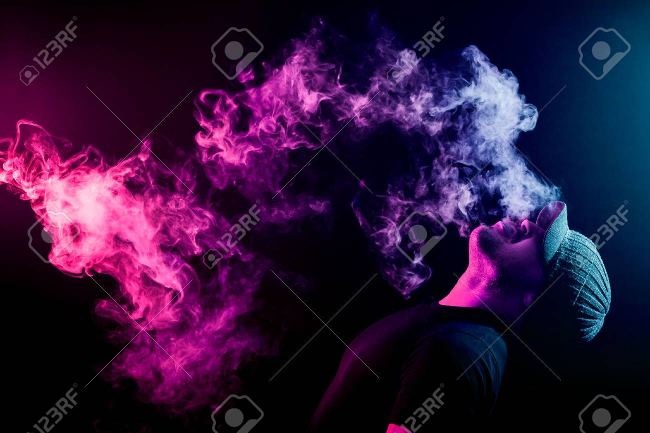Vaping man holding a mod. A cloud of vapor. Black background. Vaping an electronic cigarette with a lot of smoke. Vape concept - 92995502