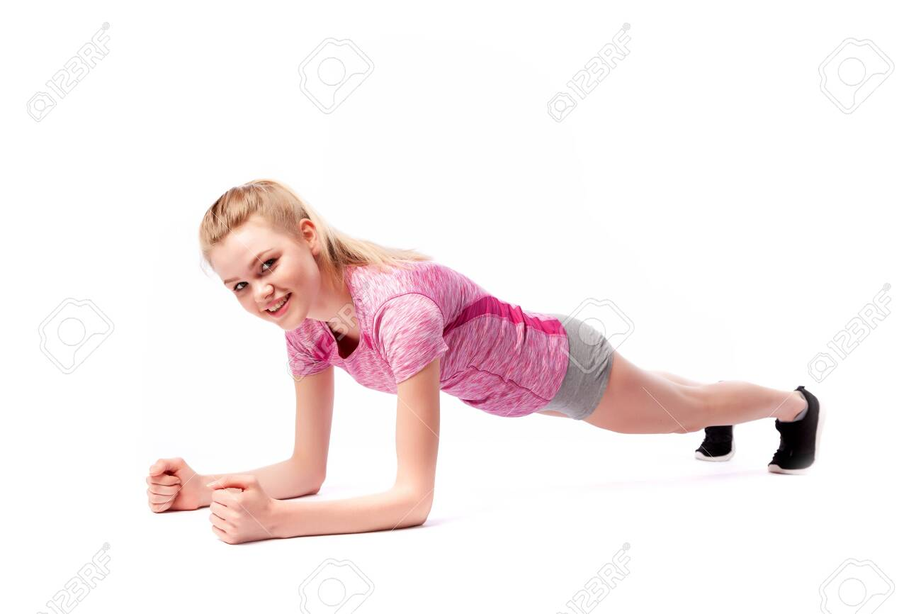 Young woman in sports clothes smilling, possing and standing on the arms in the plank position on the floor on white isolated background. Side view.Fit girl living an active lifestyle - 122704800