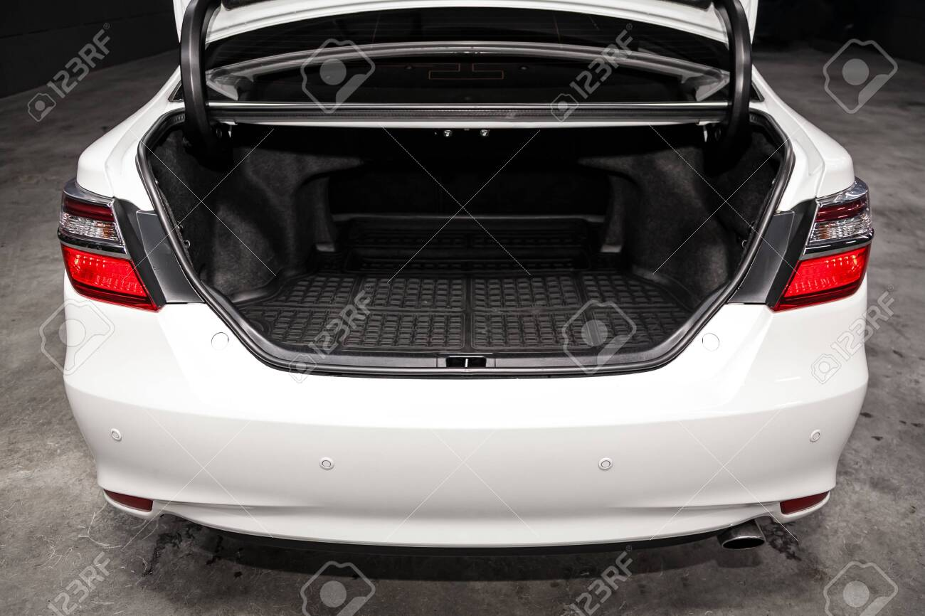 Close up Rear view of a sedan white car with open trunk in garage. Empty car trunk - 124874103