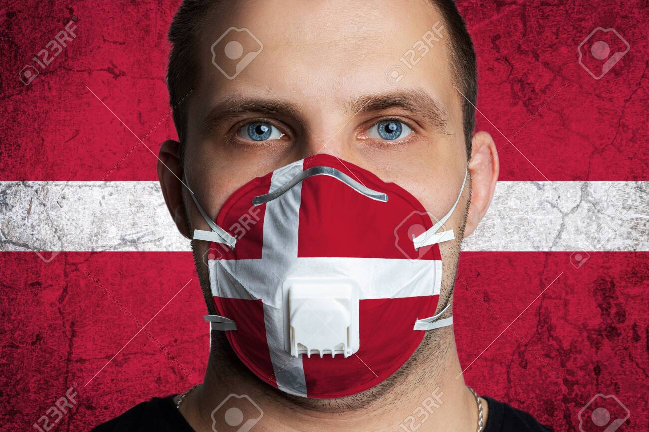 Young man with sore eyes in a medical mask painted in the colors of the national flag of Denmark. Coronovirus disease COVID-19 concept. Man is afraid of getting the flu - 144301668
