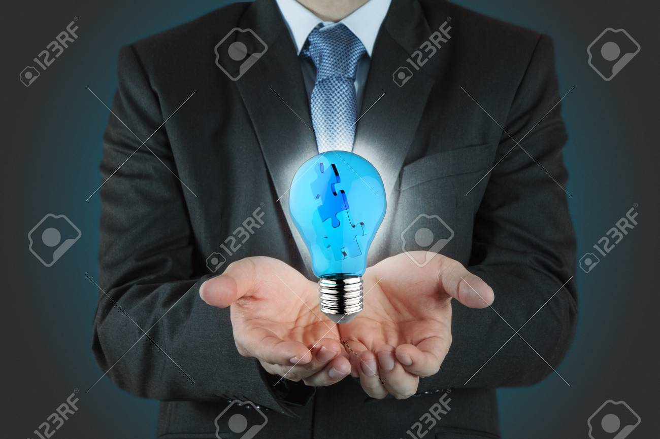 businessman hand shows light and puzzle partnership Stock Photo - 16707181