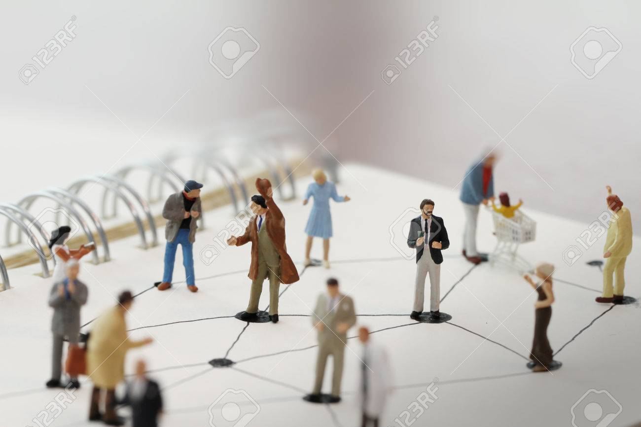 close up of miniature people with social network diagram on open notebook on wooden desk as social media conept - 38163344