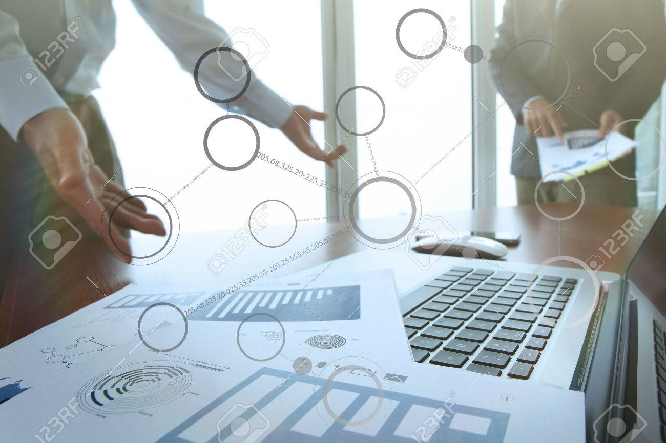 business documents on office table with smart phone and digital tablet and stylus and two colleagues discussing data in the background - 41473148
