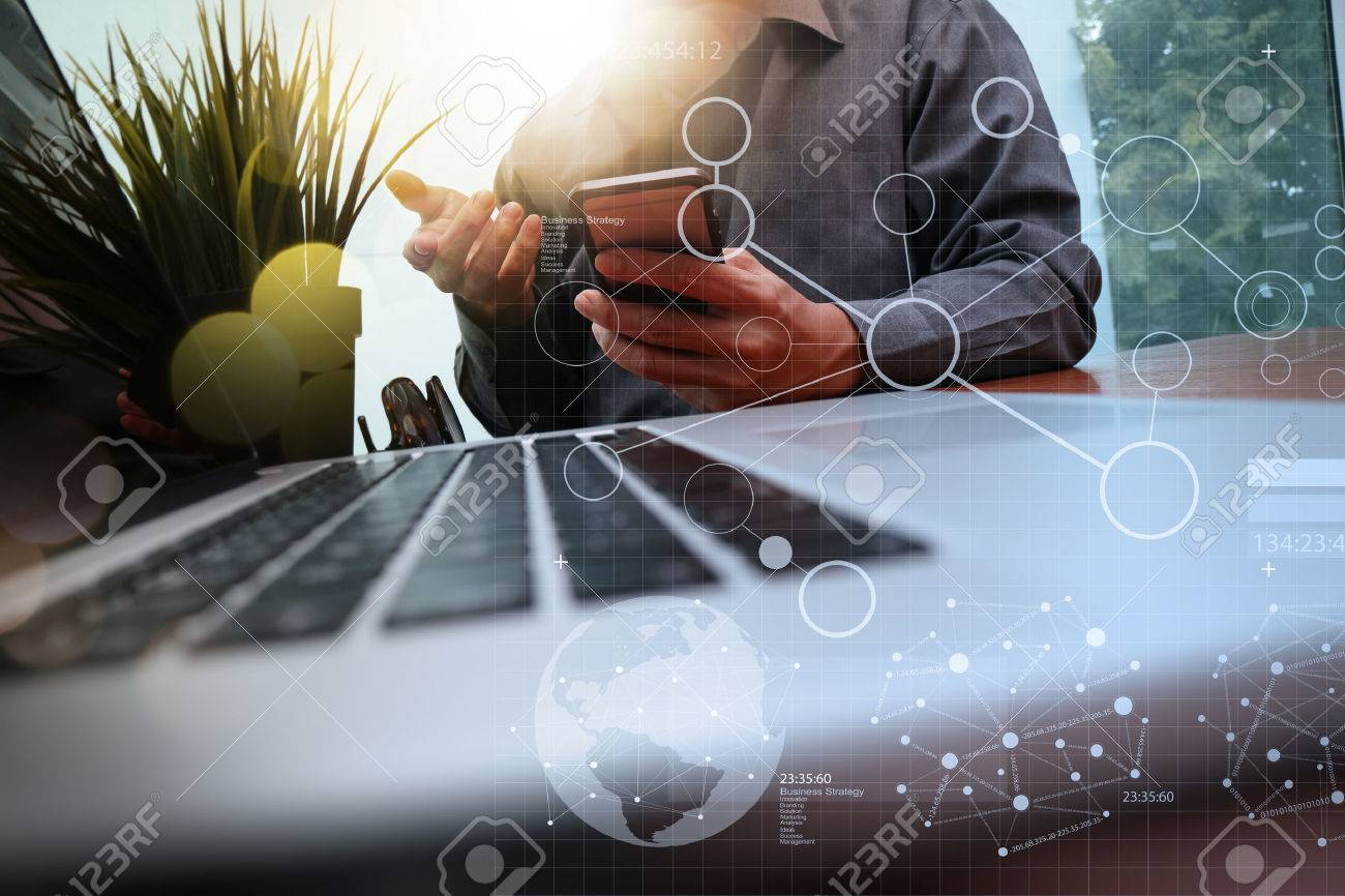 businessman hand working with new modern computer and business strategy documents digital layers with green plant foreground on wooden desk in office - 50068964