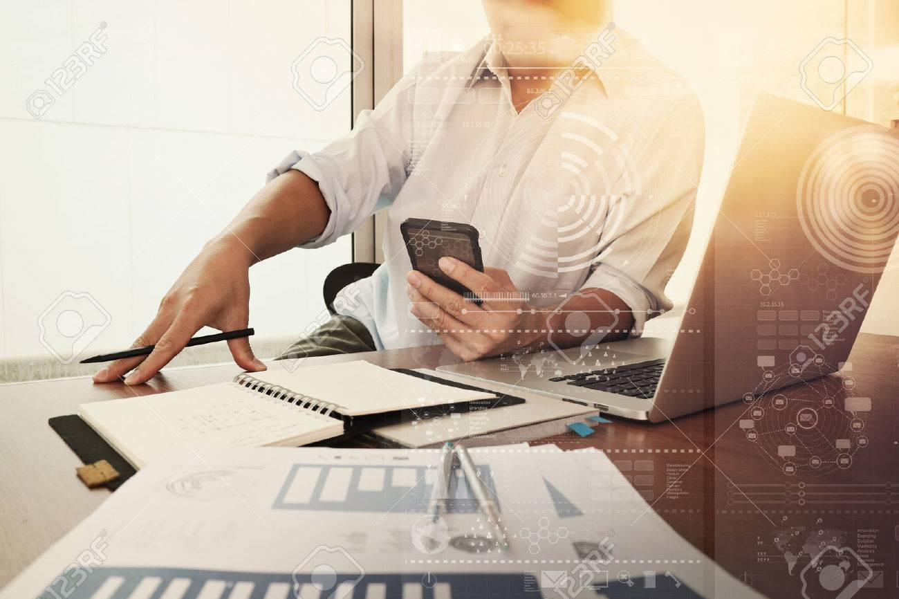 business documents on office table with smart phone and laptop computer and graph business diagram and man working in the background - 50068968