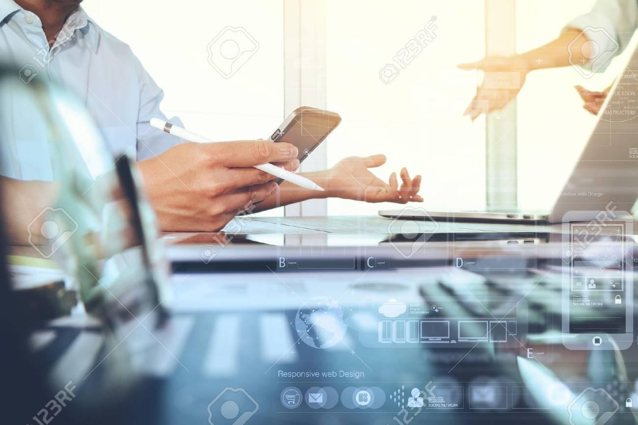 Geschäftsunterlagen auf Büro-Tabelle mit Smartphone und Laptop-Computer und Grafik Geschäft mit sozialen Netzwerkdiagramm und zwei Kollegen diskutieren im Hintergrund Daten Standard-Bild - 51496866