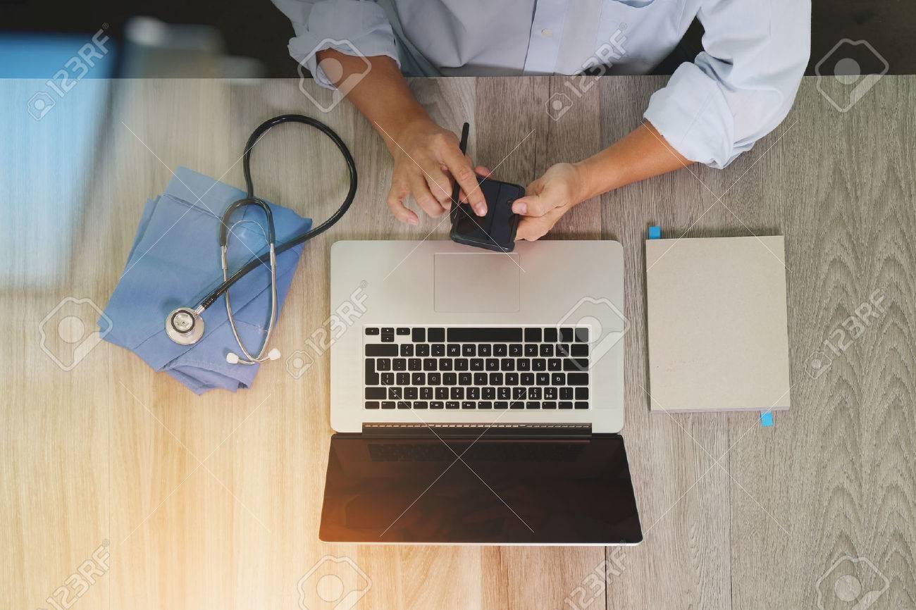 Draufsicht Medizin Arzt der Hand die Arbeit mit modernen Computer-und Smartphone auf Schreibtisch aus Holz, wie medizinische Konzept Standard-Bild - 51496795