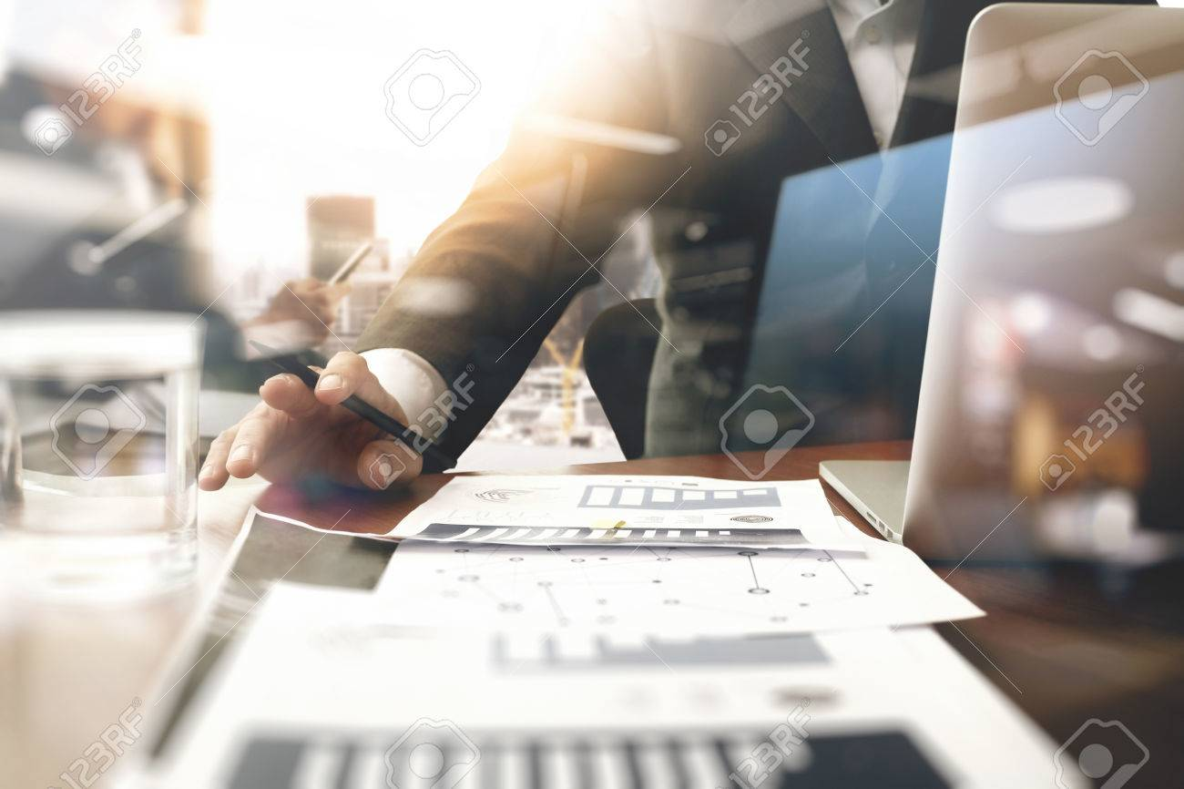 business documents on office table with smart phone and blank screen laptop computer and graph business diagram and two colleagues discussing data in the background - 58966899