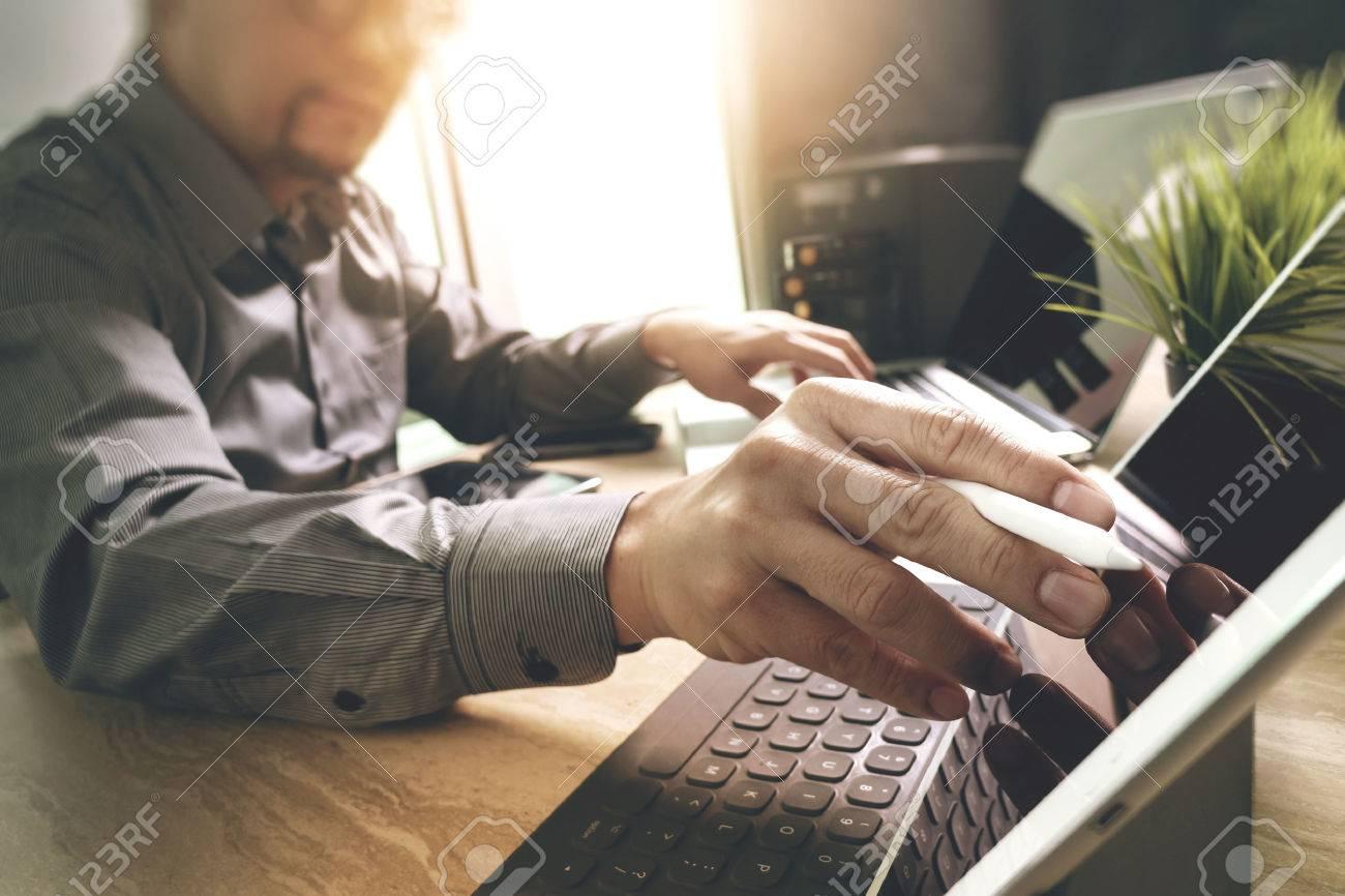 Outsource Developer working on marble Desk Working Laptop Computer Mobile Application Software and digital tablet dock smart keyboard,compact server,sun flare effect Standard-Bild - 64119124