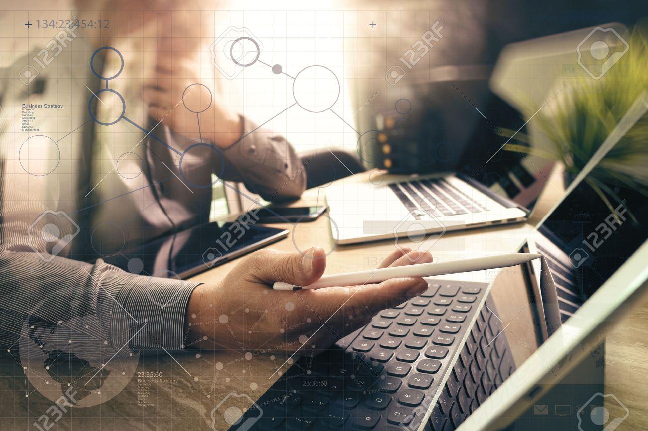 Outsource Developer working on marble Desk Working Laptop Computer Mobile Application Software and digital tablet dock smart keyboard,compact server,sun flare effect Standard-Bild - 64116288