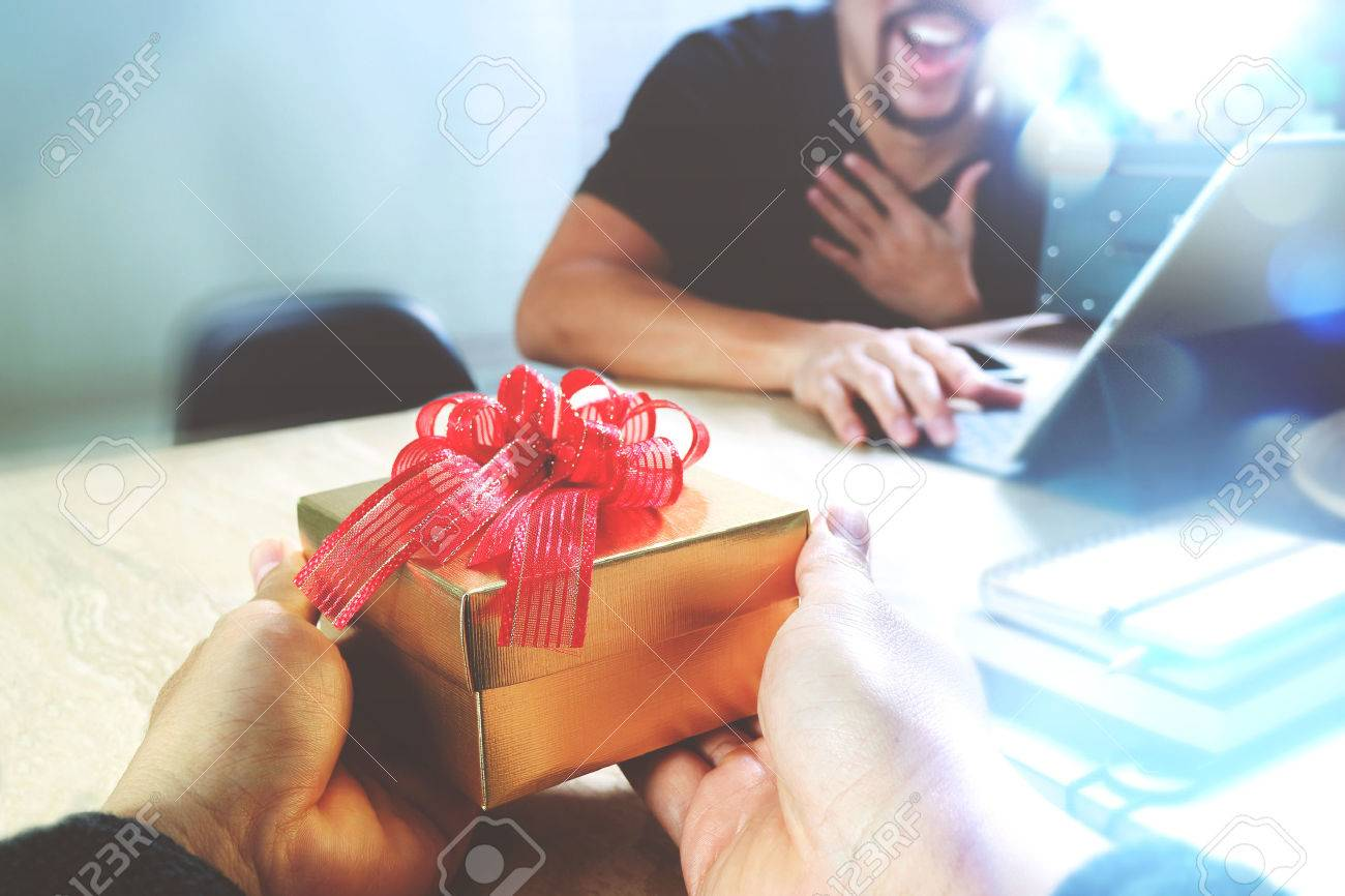 Gift Giving.business creative designer hand giving his colleague Christmas present in office,filter film effect - 65502226