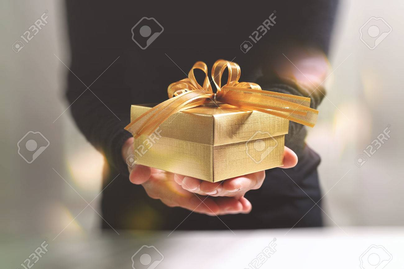 gift giving,man hand holding a gold gift box in a gesture of giving.blurred background,bokeh effect Standard-Bild - 64893105