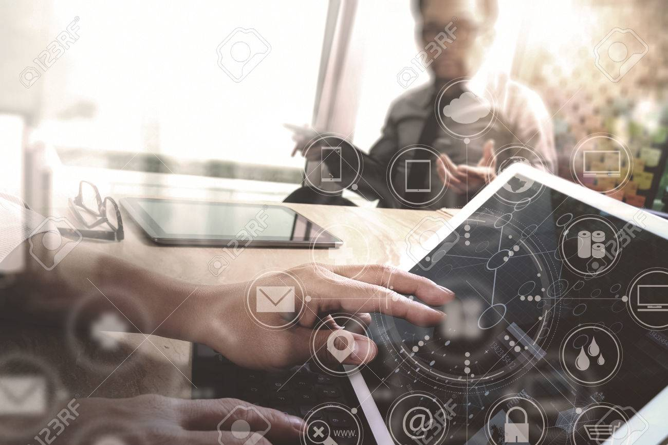 Co worker Designer hand using mobile payments online shopping,omni channel,in modern office wooden desk,icons graphic interface screen,eyeglass,filter Banque d'images - 68573907