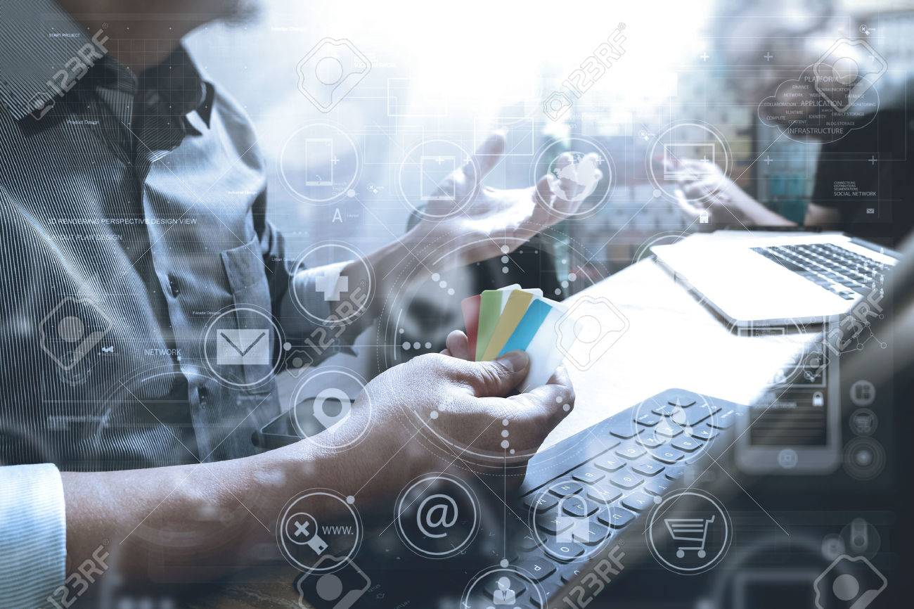 Co worker Designer hand using mobile payments online shopping,omni channel,in modern office wooden desk,icons graphic interface screen,eyeglass,filter - 68573814