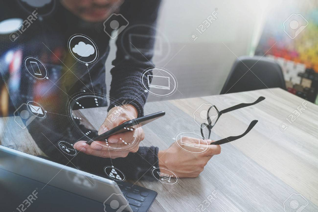 Businessman hand using mobile payments online shopping,omni channel,in modern office wooden desk,icons graphic interface screen,eyeglass - 68573963