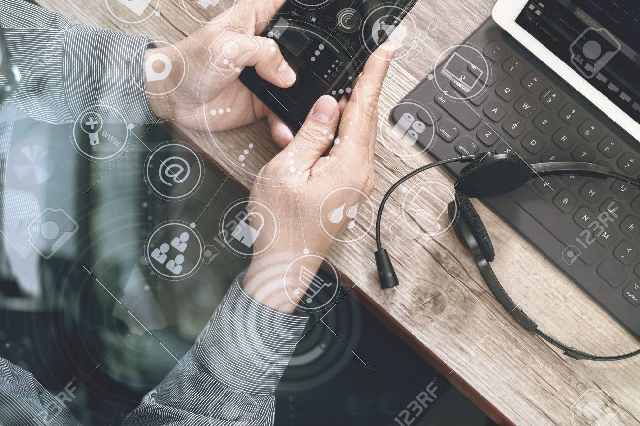 top view of man hand using VOIP headset with digital tablet computer docking keyboard,smart phone,concept communication, it support, call center and customer service help desk on wooden table,virtual interface icons screen Standard-Bild - 70550724