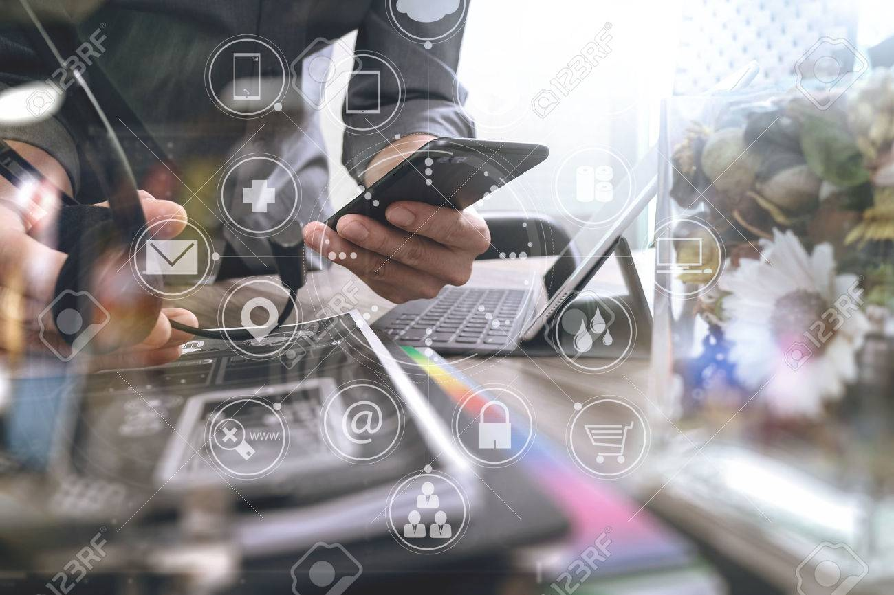 Man using VOIP headset with digital tablet computer docking keyboard,smart phone,concept communication, it support, call center and customer service help desk,vase flowers on wooden table,business strategy icons interface virtual screen - 70554674