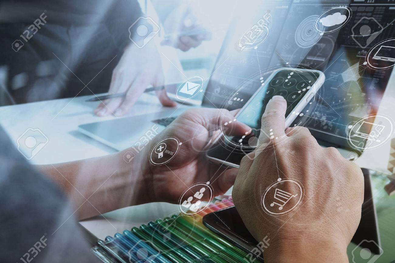Designer Businessman hand using smart phone,mobile payments online shopping,omni channel,digital tablet docking keyboard computer in modern office on wooden desk,virtual interface icons screen Standard-Bild - 70554706