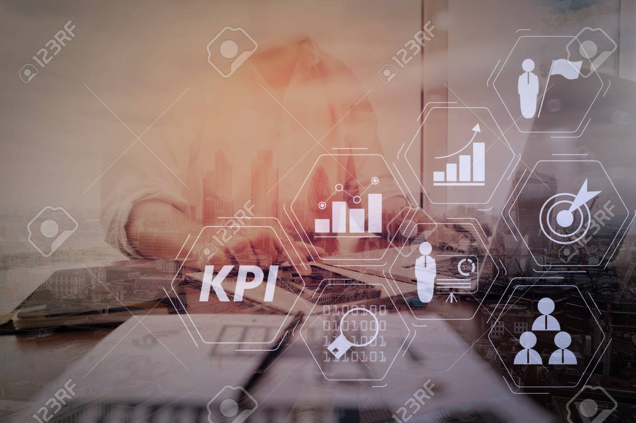 Key Performance Indicator (KPI) workinng with Business Intelligence (BI) metrics to measure achievement and planned target.businessman working with smart phone and laptop computer on wooden desk. - 101656879