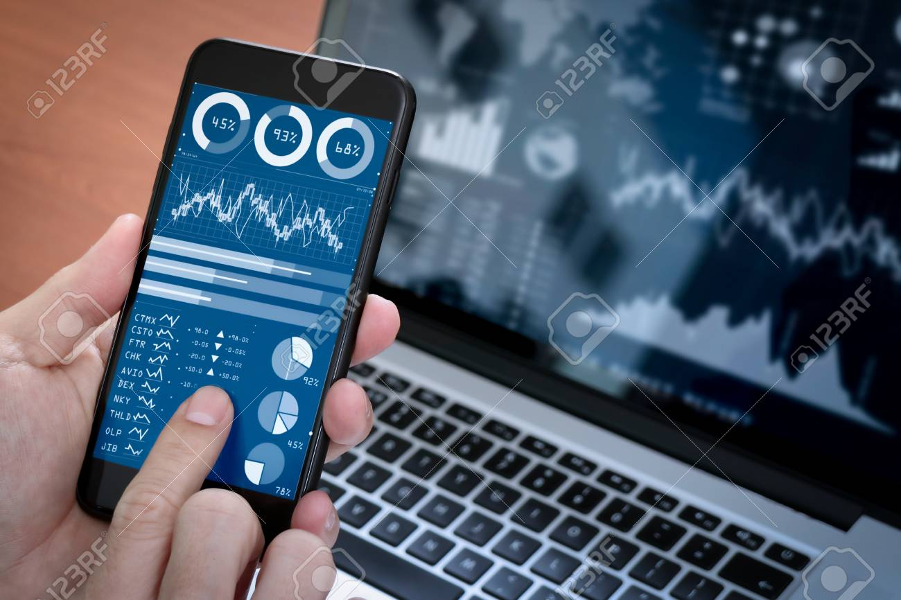 Investor analyzing stock market report and financial dashboard with business intelligence (BI), with key performance indicators (KPI).Businessman using smart phone with laptop computer. - 101658352