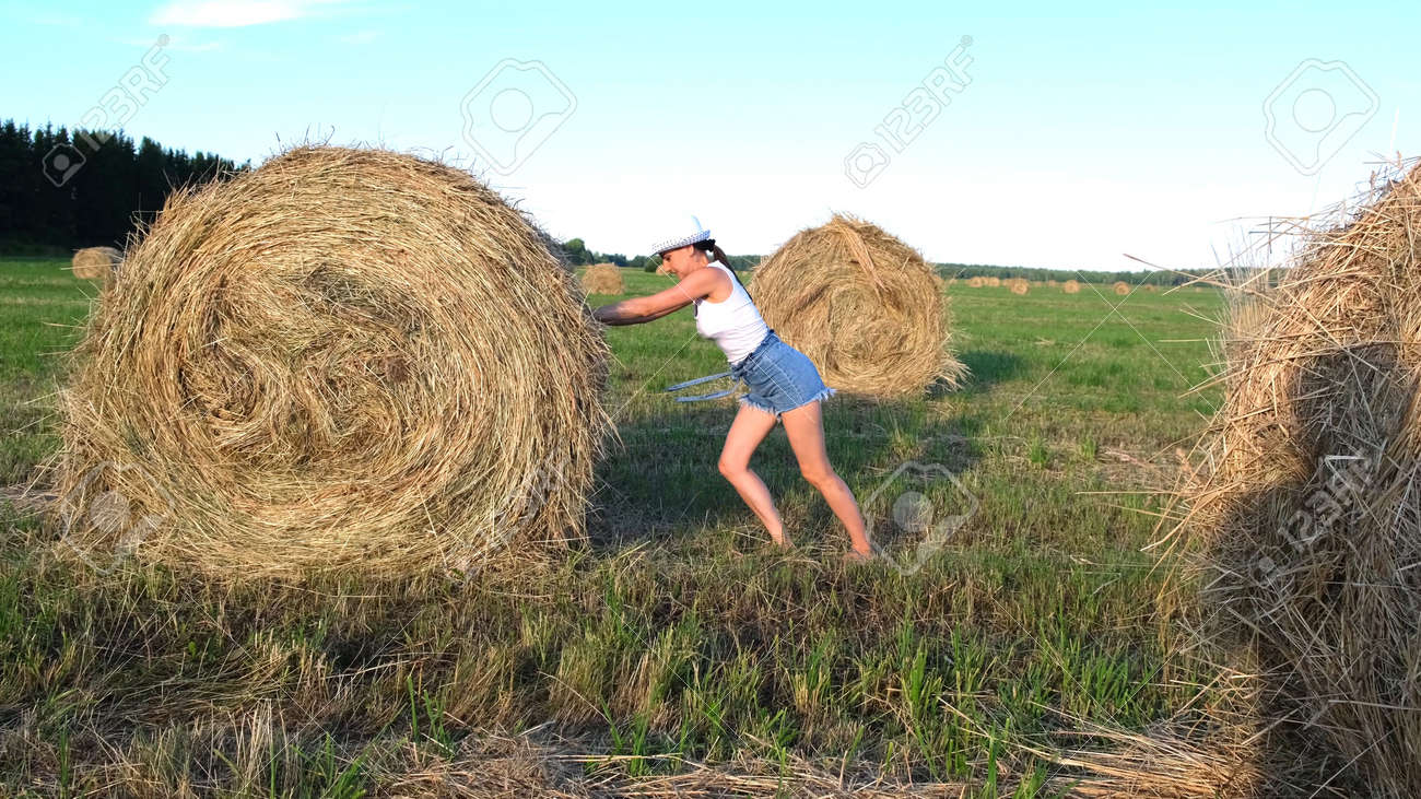 beautiful young girl in a hat pushes a haystack. Rural area. Feminist strong woman concept. - 171399569