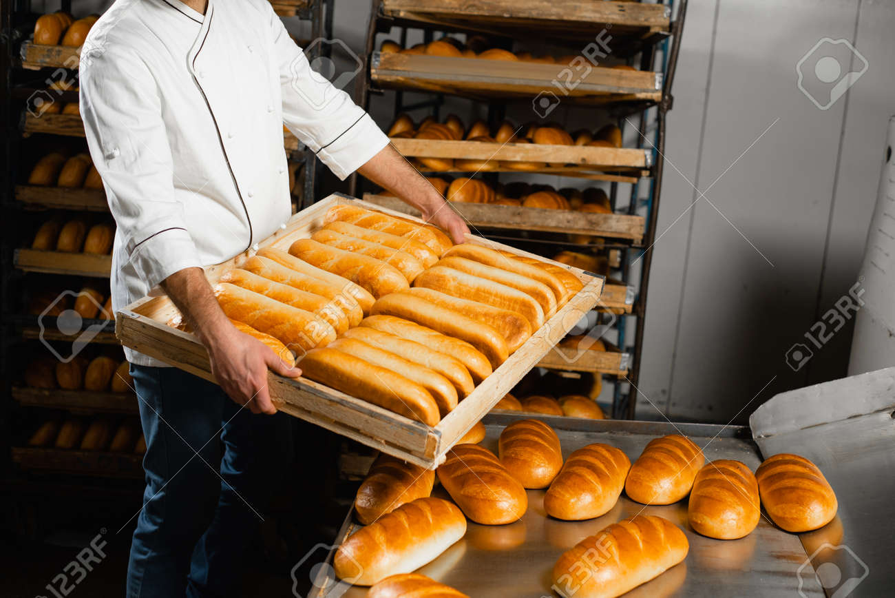 The baker holds a wooden box with hot bread on the background of shelves with bread in the bakery. Industrial bread production - 152194149
