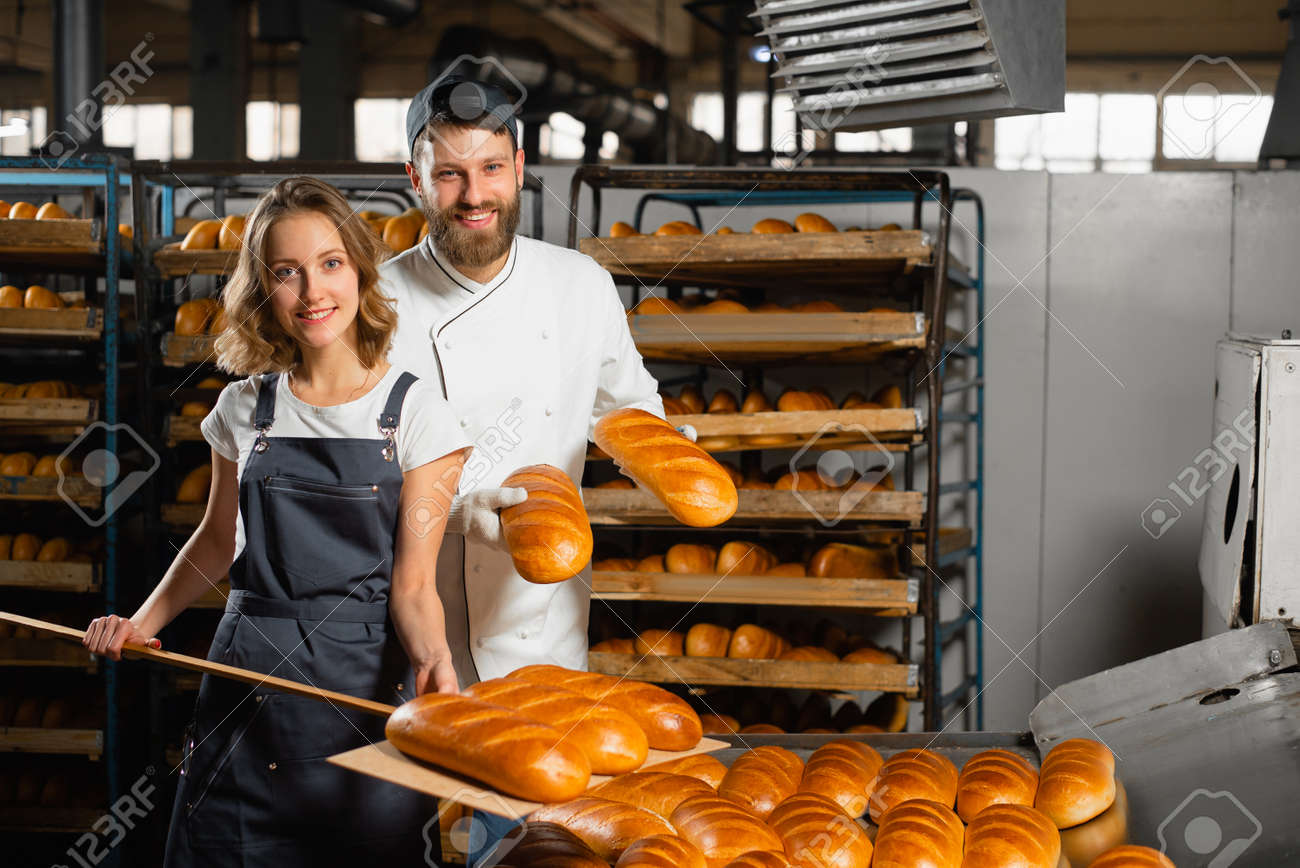 Young bakers with a wooden shovel with bread in their hands against the background of shelving with bread in a bakery. Industrial bread production - 152193965