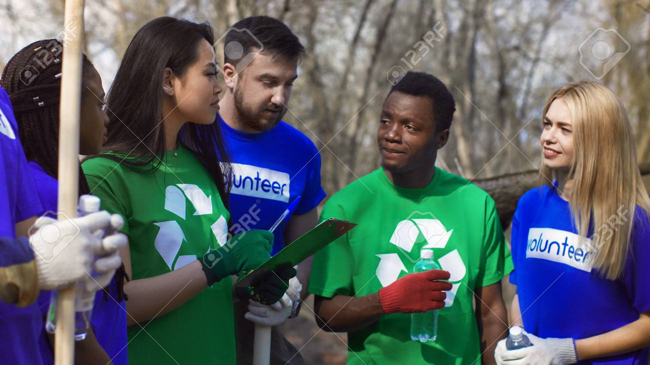 Stock Photo - Young Asian girl with clipboard coordinating diverse  volunteers for work of cleanup in spring forest.