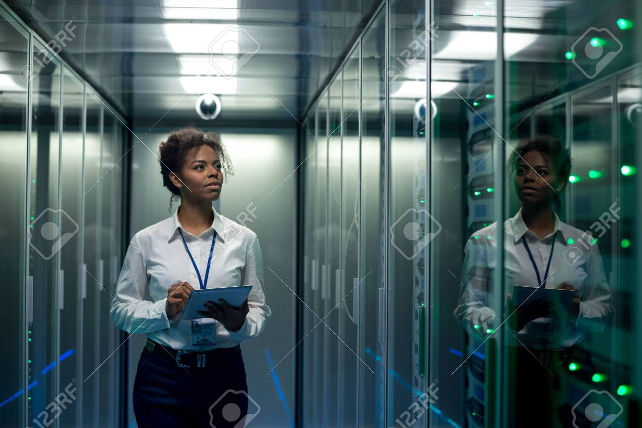 African American woman using tablet while walking in corridor of data center and checking hardware on server racks - 121128514