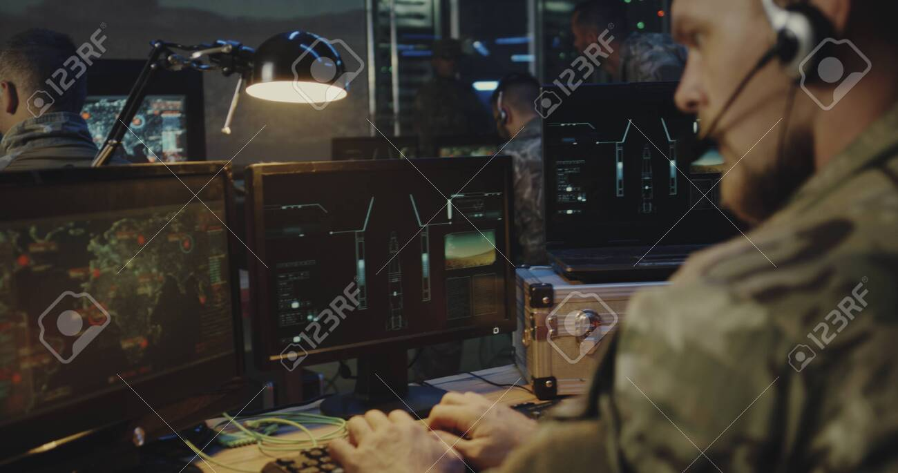 Medium close-up of soldiers controlling rocket launch on computer - 130501663