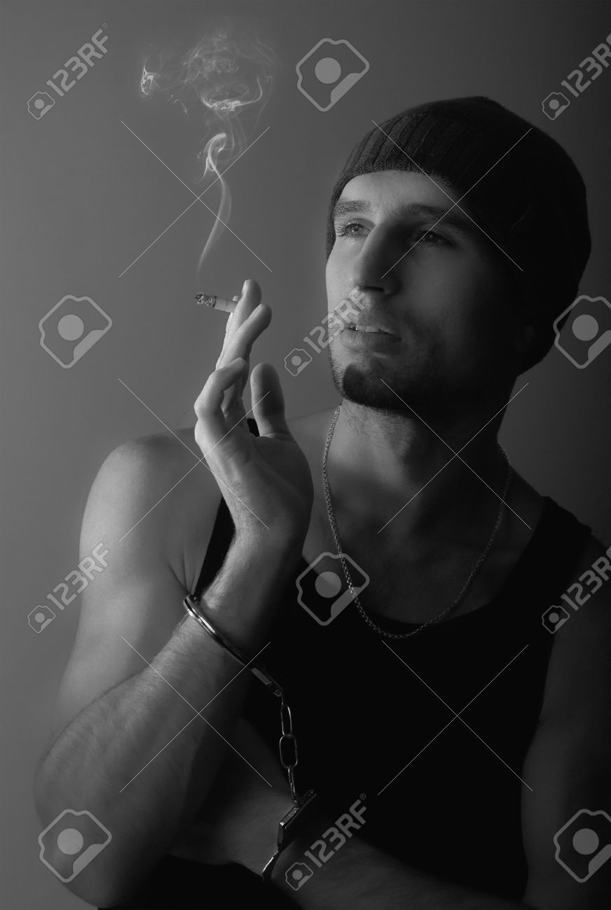 bad man in handcuffs with a cigarette Stock Photo - 11533733