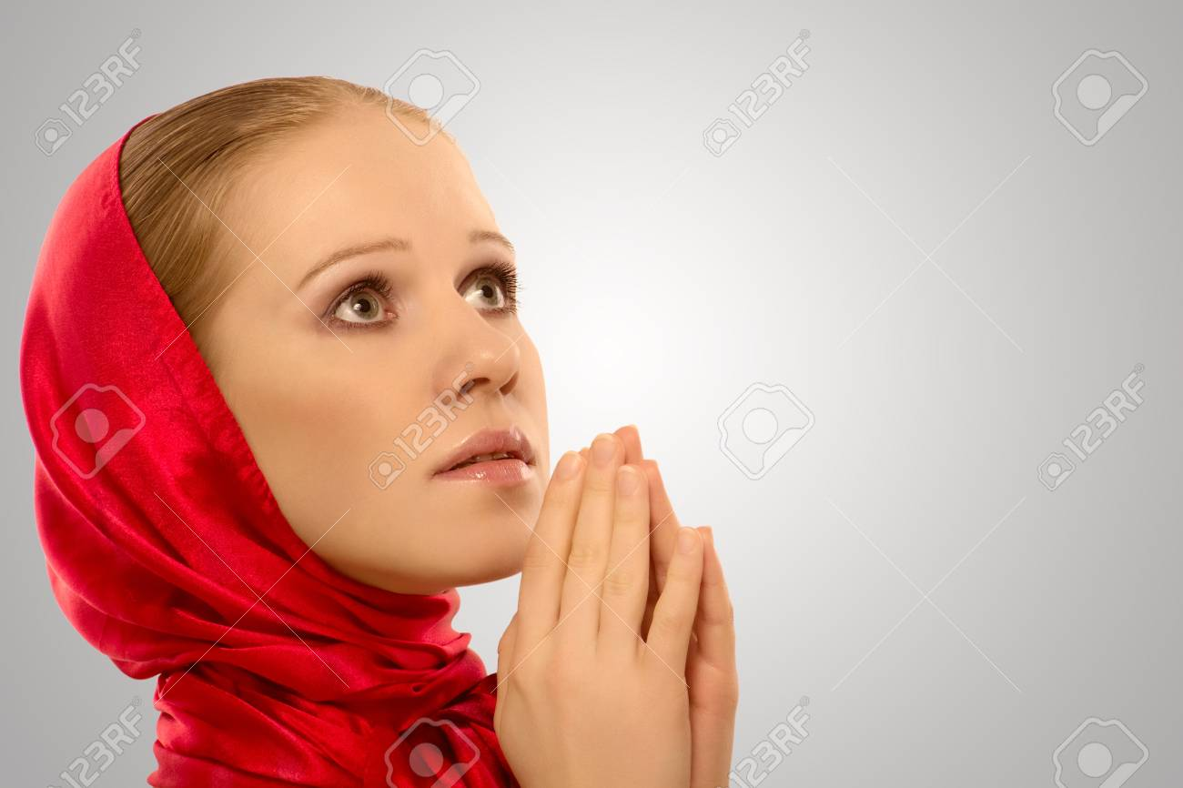 young religious woman in a red shawl prays to God Stock Photo - 13434022