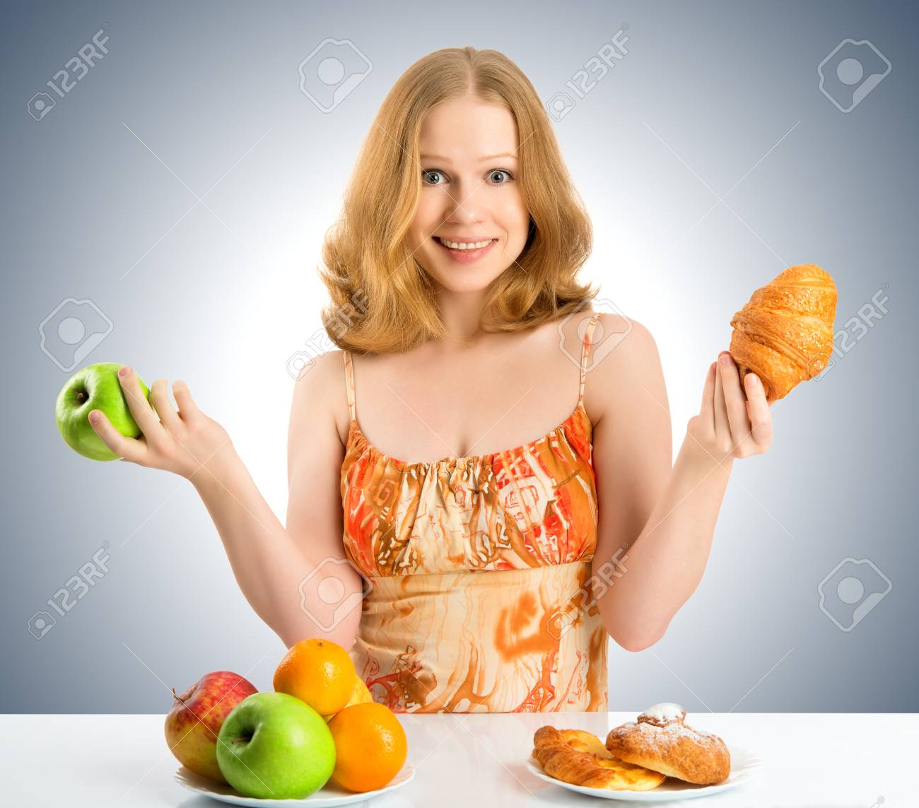 woman with a buns and fruits choose between healthy and unhealthy food Stock Photo - 18957775