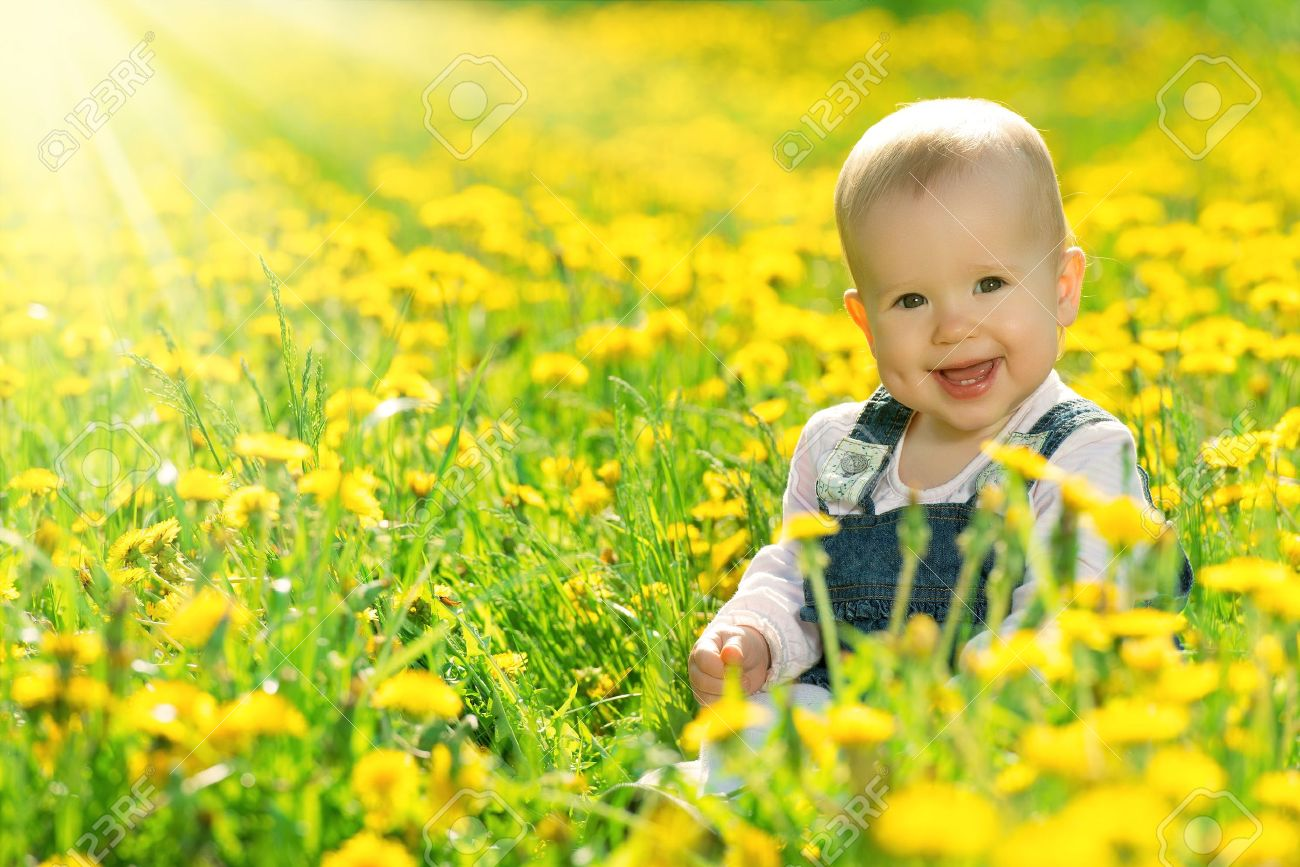 Beautiful happy little baby girl sitting on a green meadow with