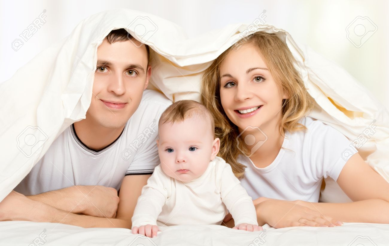 Happy family in bed under a blanket mother father baby stock photo