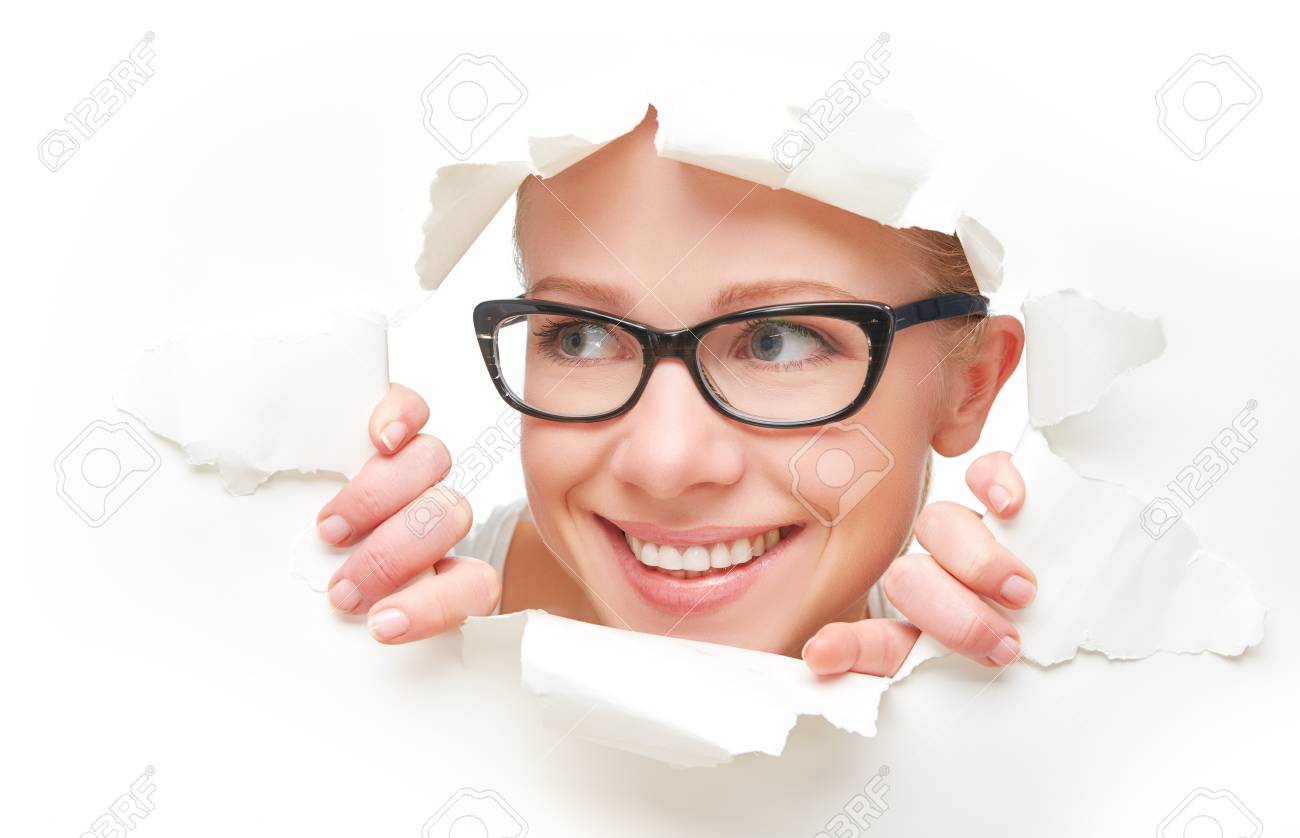face of a young curious woman in glasses peeking through a hole torn in white paper poster - 94300517