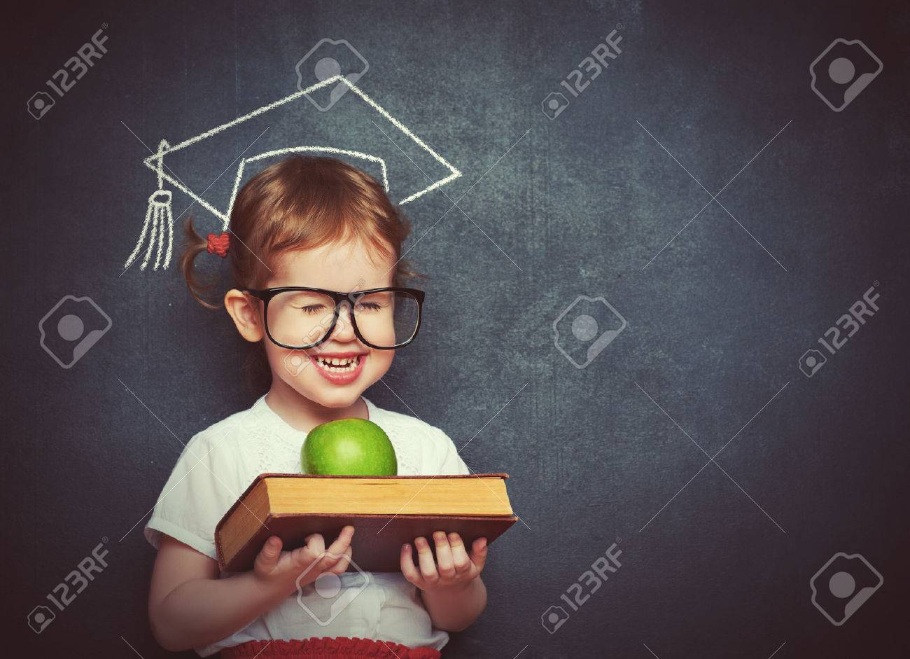 pretty little girl schoolgirl with books and apple in a school board - 39209178