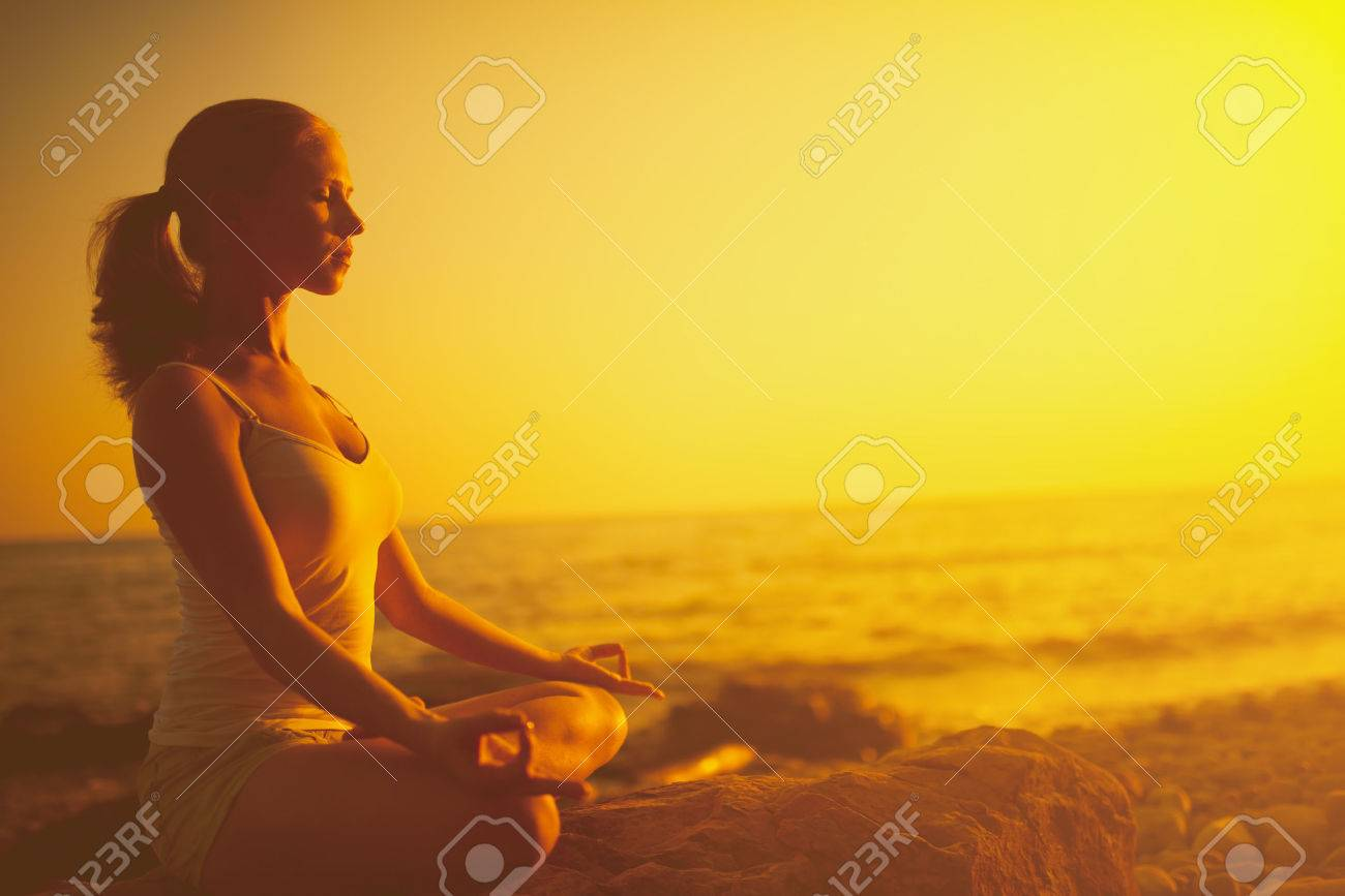 yoga in the beach. woman meditating in lotus pose on the beach at sunset - 41163869