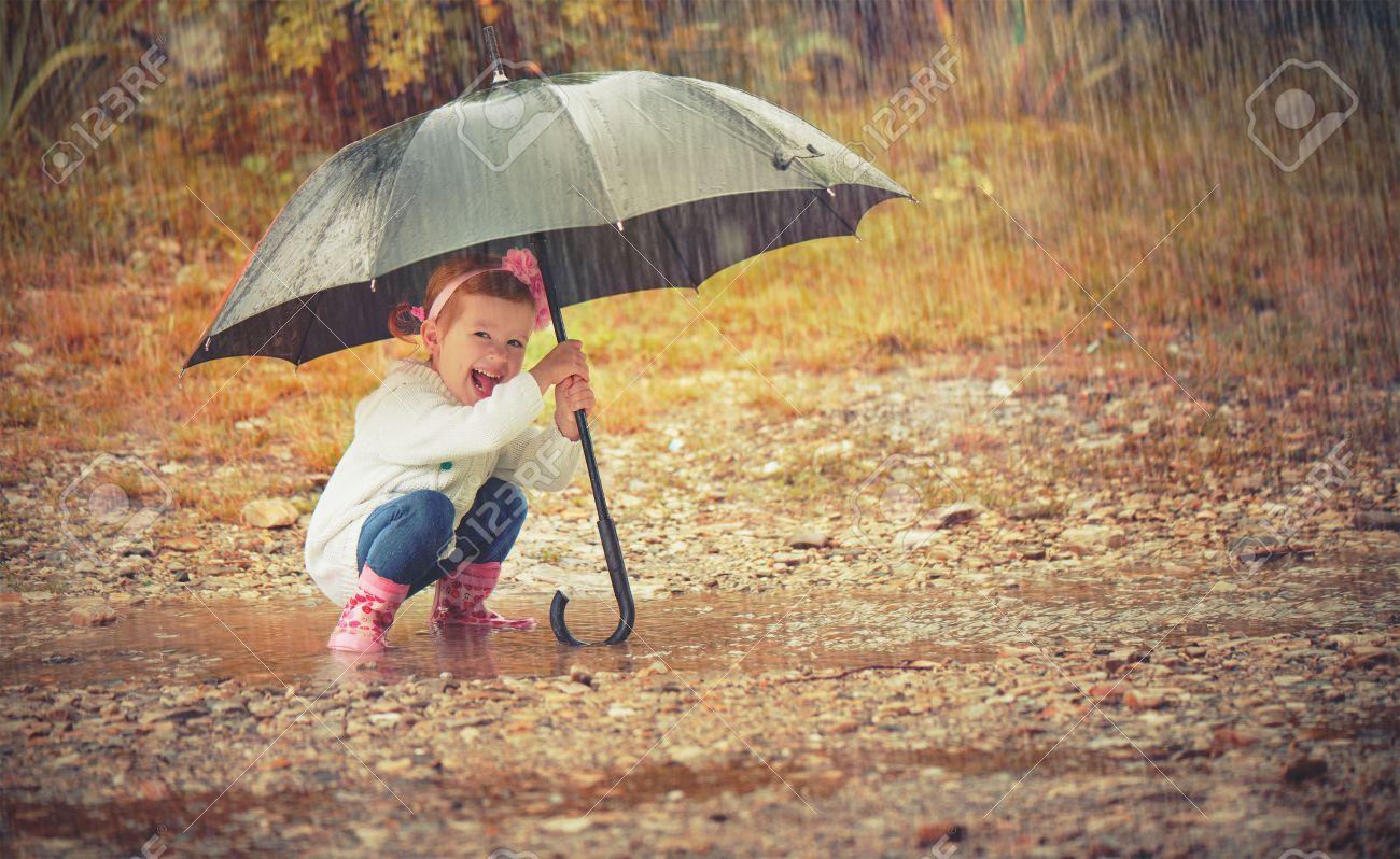 happy baby girl with an umbrella in the rain runs through the