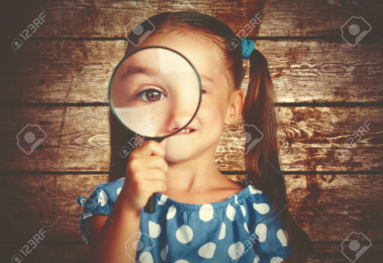 child girl playing with a magnifying glass in the detective - 43635326