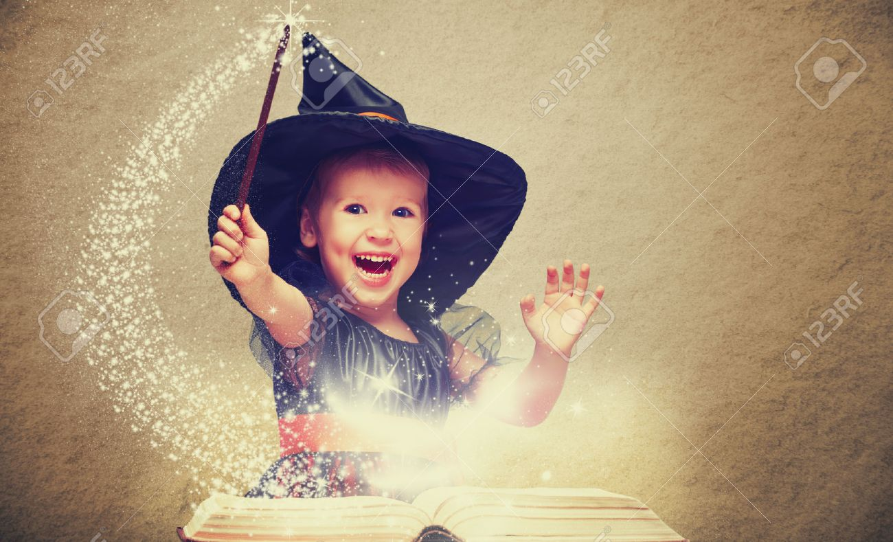 Halloween. cheerful little witch with a magic wand and glowing book conjure and laughs. - 45560726