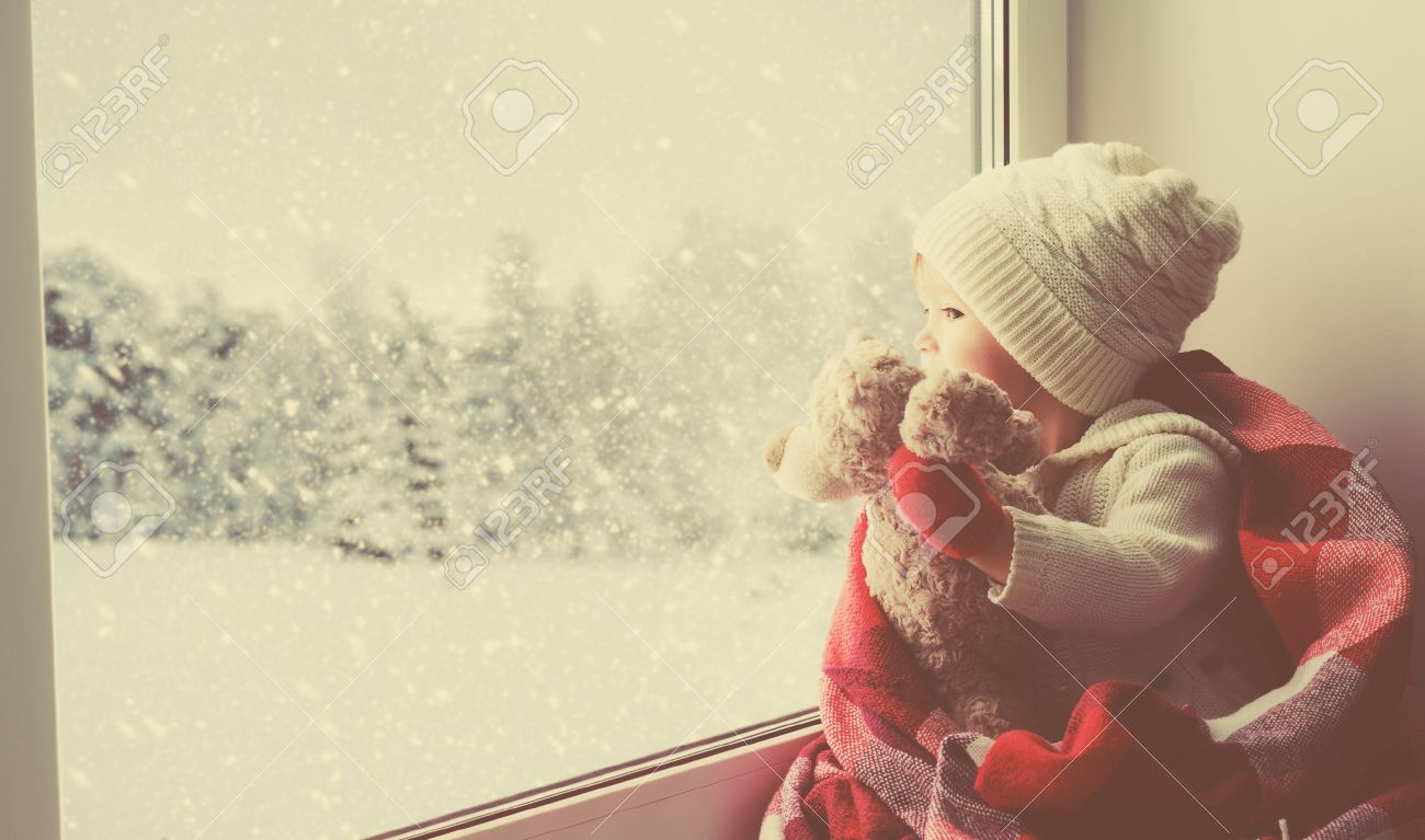 child little girl sitting by the window with a teddy bear and looking at the winter forest - 48969138