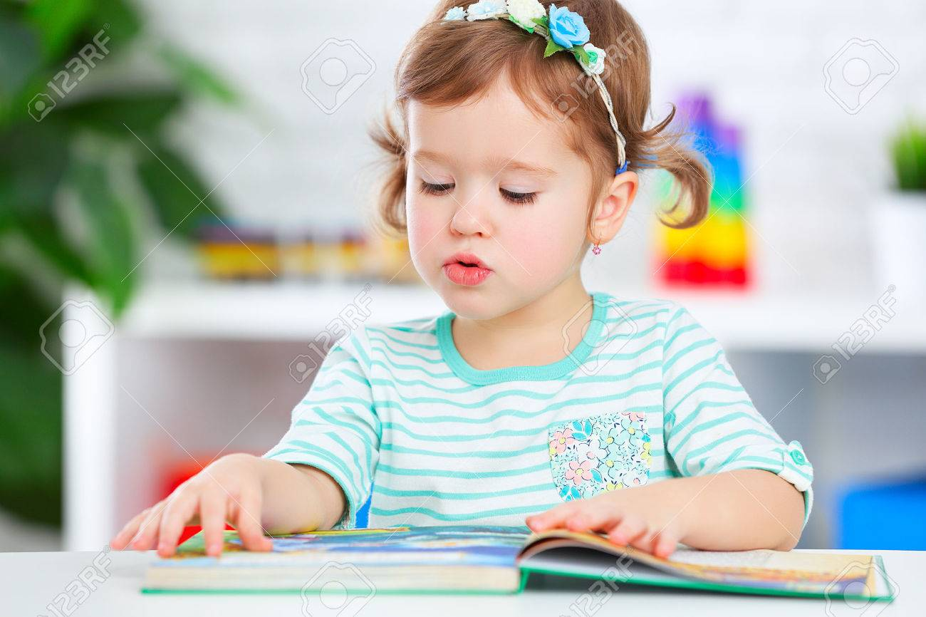 cute baby girl reading a book at home stock photo, picture and