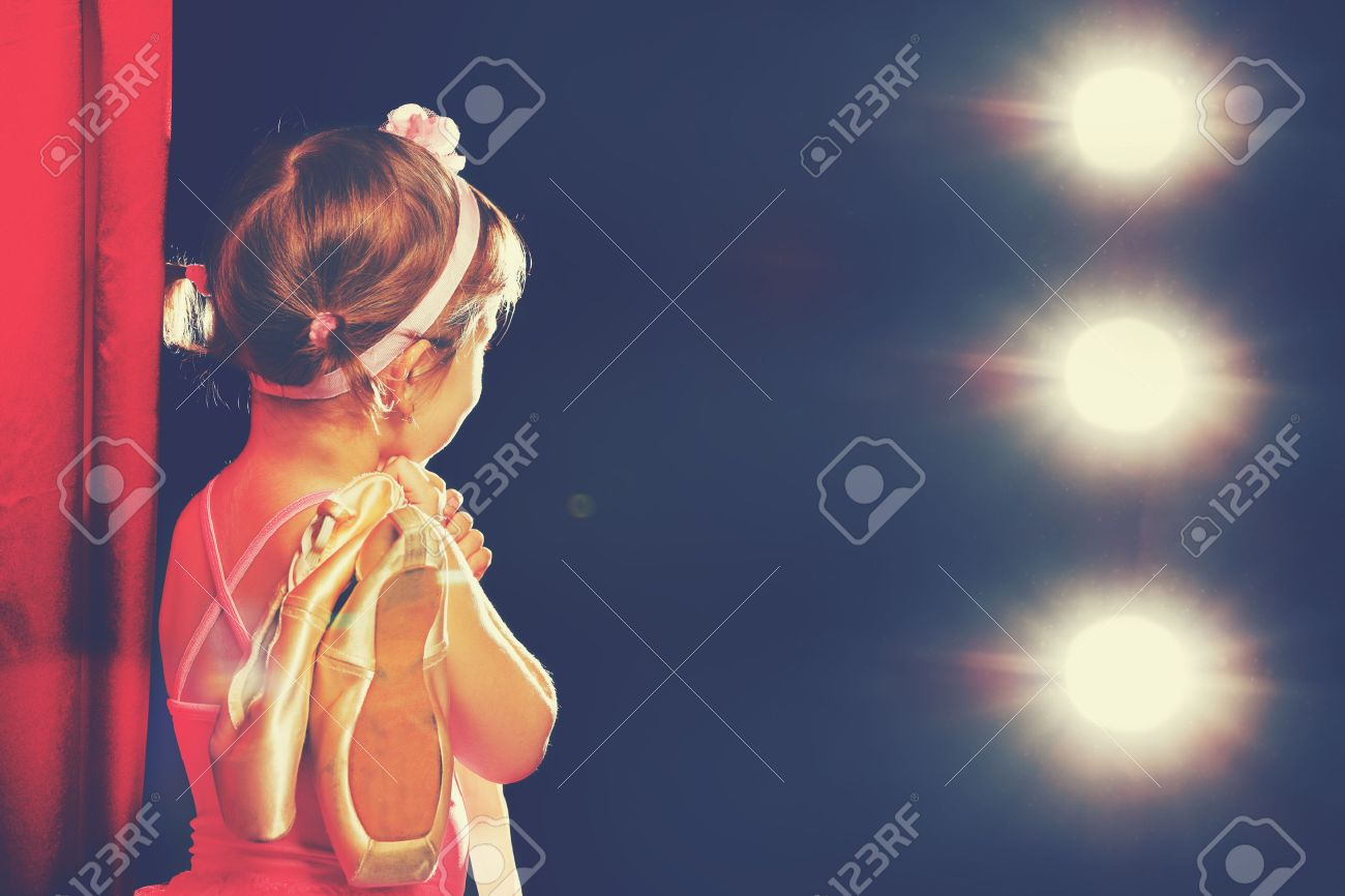 little child girl ballerina ballet dancer on the stage in red side scenes and looking in odeum - 50572967