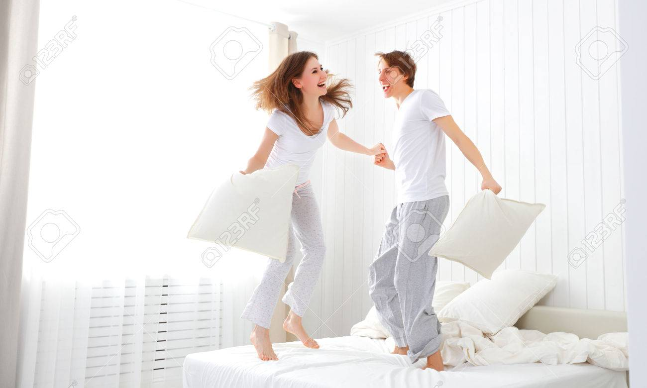 Happy loving couple jumping and having fun in bed - 50575991