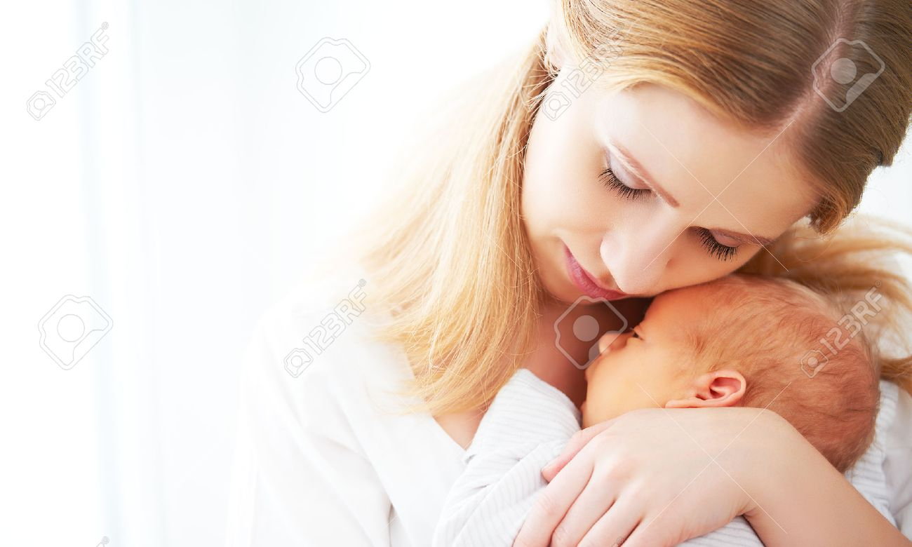 newborn baby in a tender embrace of mother at the window Stock Photo - 50758244