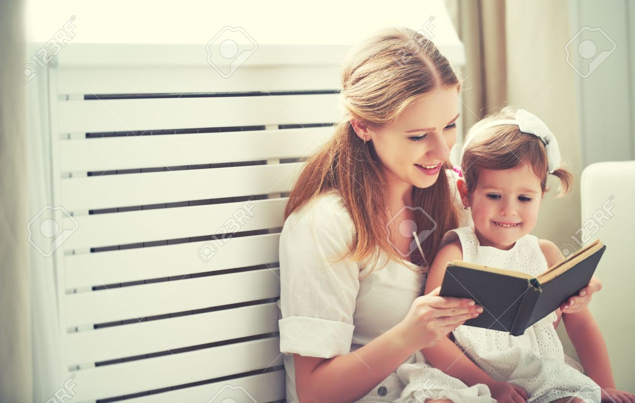 happy family mother child daughter little girl reading a book by the window - 51203924
