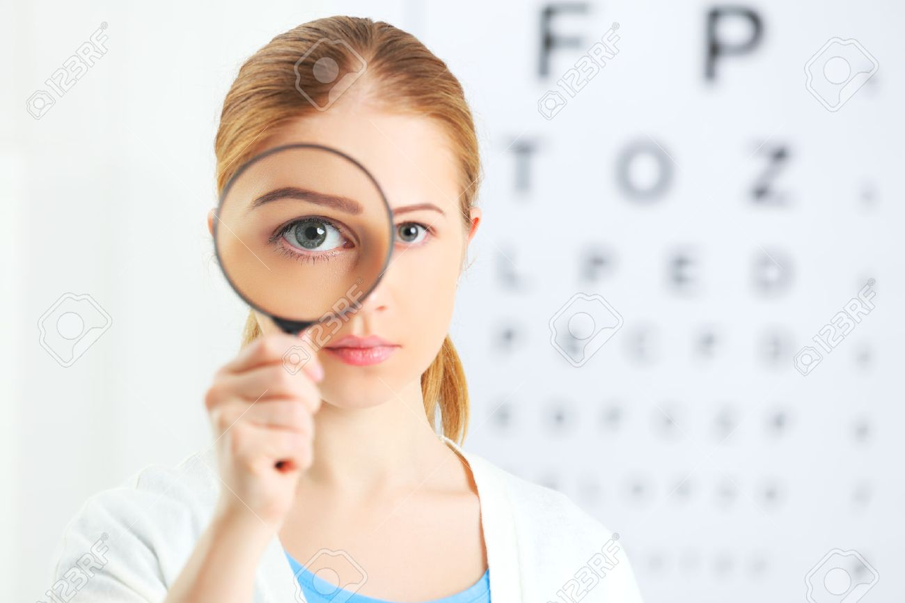 concept vision testing. woman with a magnifying glass at the doctor ophthalmologist - 51236149