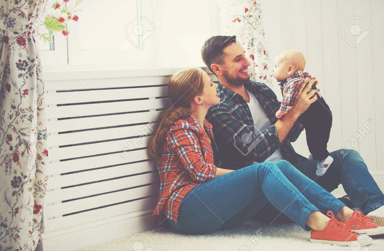 happy family mother and father playing with a baby at home - 52156050