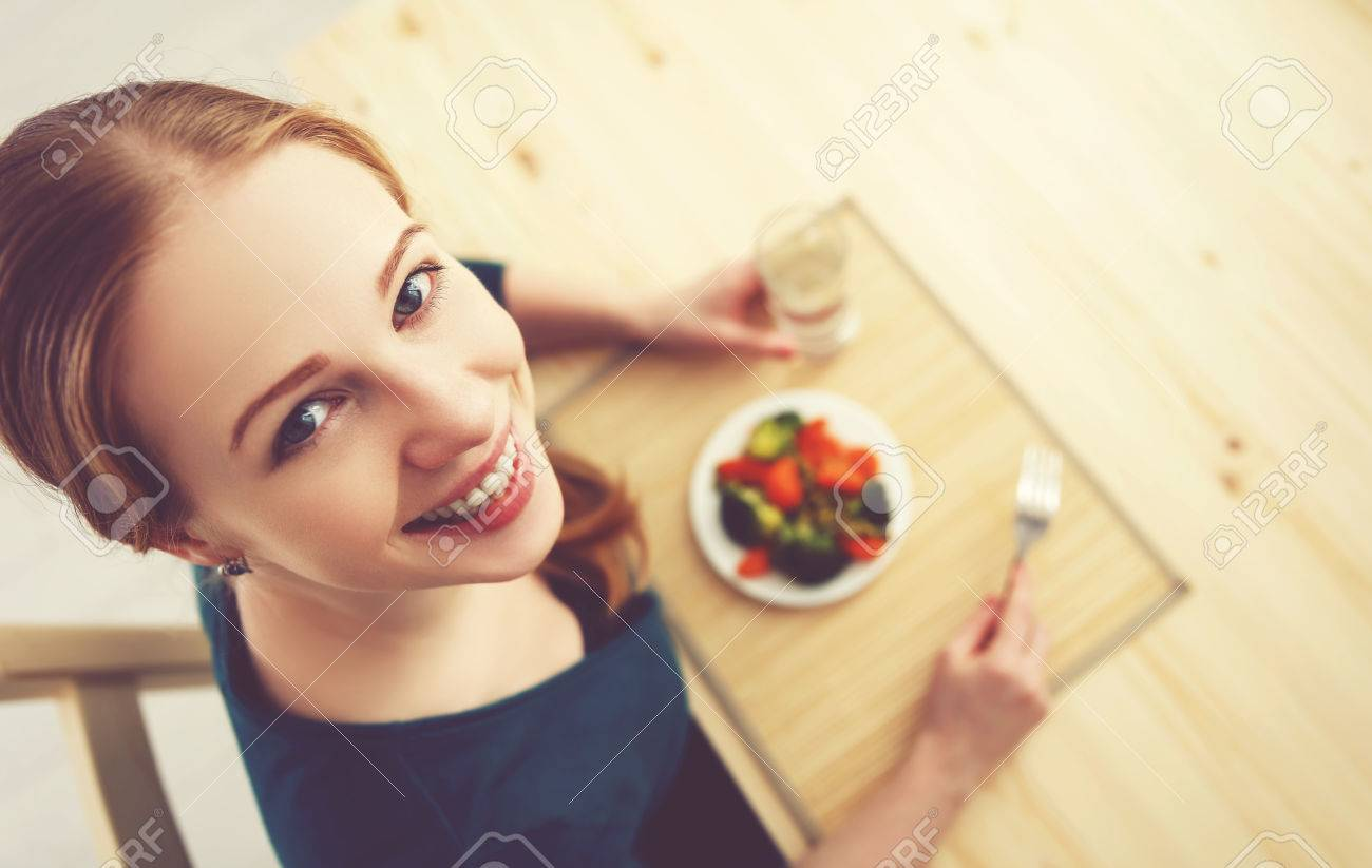 young healthy woman eats vegetables at home in the kitchen summer - 51917596